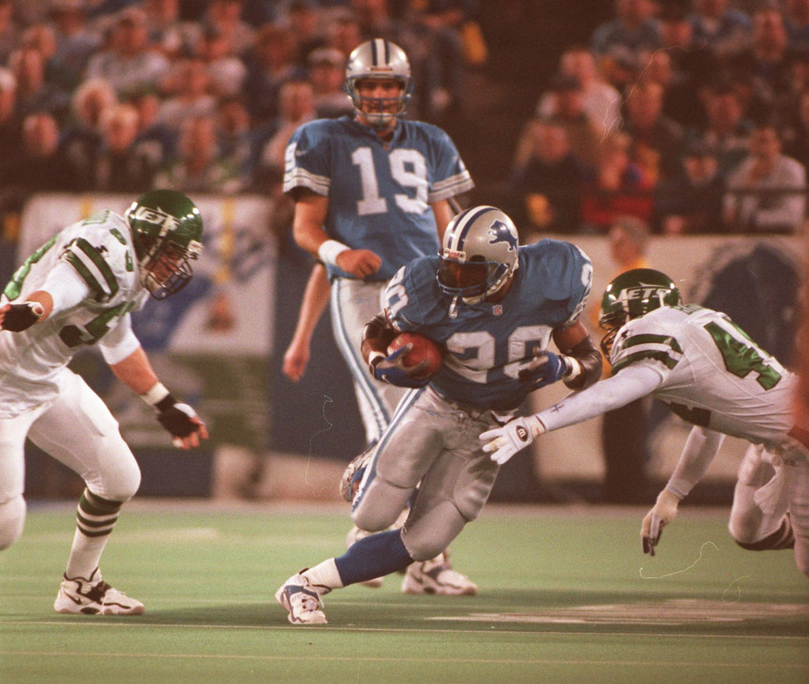 . Lion Barry Sanders splits two NY Jets in the 2nd quarter at the Silverdome. Sanders is trying to finish with over 2000 yards and a win puts the Lions in the playoffs.