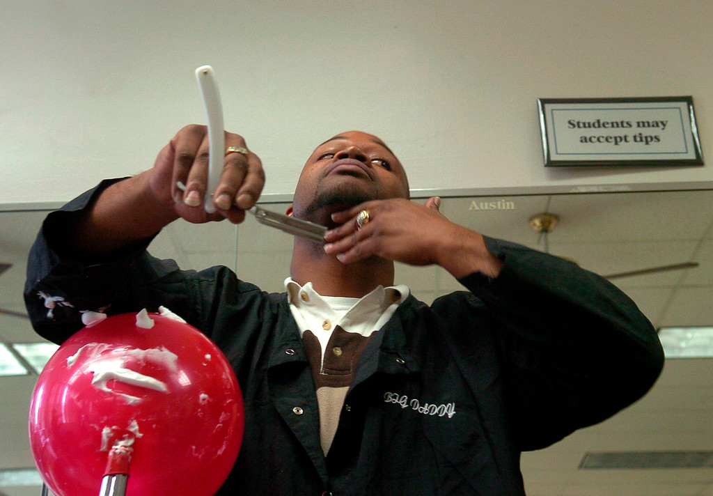 . Barber students at the Emily Griffith Opportunity School learn the correct shaving techniques of shaving by using a blown up balloon, shaving cream, and a razor in 2008. These are level one students who must complete four levels to complete their credit hours and then take the state exam to get licensed. It takes each students about nine months to complete all the levels. Level one student James Griffin practices the razor strokes in the air as instructor Sharon Salvo shouts out the techniques one by one.  Kathryn Scott Osler, The Denver Post