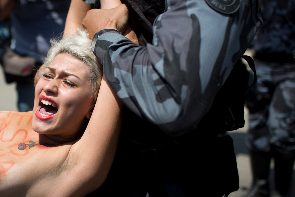 . A FEMEN activist is carried away by police while protesting the eviction of indigenous people being from the old Indian Museum in Rio de Janeiro, Friday, March 22, 2013. Police in riot gear invaded an old Indian museum complex Friday and pulled out a few dozen indigenous people who for months resisted eviction from the building, which will be razed as part of World Cup preparations next to the legendary Maracana football stadium. (AP Photo/Felipe Dana)
