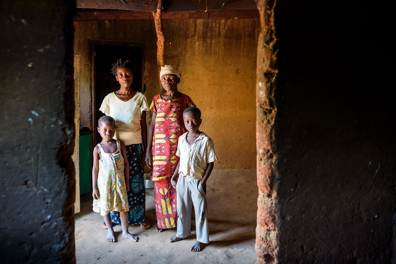 """Grace Mukoma, 10 yr-old boy, Kananga, Kasai Province, DRC, with his widowed mother, Mbombo Elize, 23, sister, Harriet, 7, and widowed grandmother, Kapinga Godelive, 66.  Background Grace lives with his mom Mbombo Elize, 23 and an extended family of relatives. Mbombo has had 4 children, the first when she was 15. 2 died during the time they had to run away because of the war. Now it's just Grace and his sister Harriet, 7.  They live in the Kasai Centrale province in a place called Katoka. It's a rural community. Grace and his family had to run when war broke out in the DRC.  His father was killed. His mother and her 4 children ran about 2 kilometers down the road from his house towards the Lualua River. They hid there for about 3 months. Unfortunately, because of a lack of food and disease, Grace's brother and a sister died. After about 3 months Grace and his family hesitantly made their way back to their house. It had been burnt and was empty. They've struggled ever since.  Here's a look at Grace's life today:  Home Life  """"Early in the morning I sweep the compound. Then I wash and if there is food I eat. Then I join my friends at the CFS."""" """"Sometimes they send me on other errands. If they need something, they send me.""""  Food Grace's family doesn't have enough food. On any given day they may or may not eat. When they do eat, it's once a day, usually in the evening. They often go to bed hungry. At the CFS they have a feeding program. When they started it they identified 200 children who were malnourished. Grace was once of them. Today they are feeding the children a porridge made from soy, corn, which they call maize, peanuts and a fruit called maringa.  Grace eats it enthusiastically.  Water Every day, Grace follows a winding, dirt path behind his house for about a mile. It leads downhill to a muddy pond. The water is brown and has a filmy covering on it. Grace rolls up his pants and wades in with a small, purple bucket which he fills up with a smaller, stainless ste"""