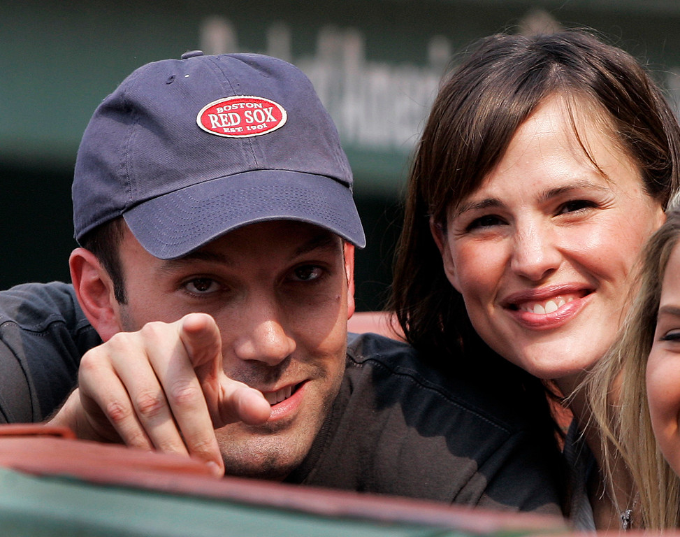 . Actor Ben Affleck points while Jennifer Garner smiles as they sit next to the Boston Red Sox dugout prior to the start of their baseball game against the New York Yankees at Fenway Park in Boston Saturday, June 2, 2007. (AP Photo/Elise Amendola)