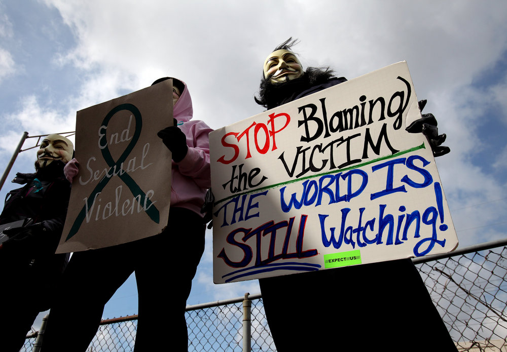 . Protesters, who did not want to be identified, hold signs outside of the Jefferson County Justice Center and Jail in Steubenville, Ohio, on Wednesday, March 13, 2013.  About 20 other demonstrators stood outside the justice center with signs and masks protesting the rape trial of Trent Mays, 17, and Ma\'lik Richmond, 16, accused of of raping a 16-year-old West Virginia girl in August of 2012. (AP Photo/The Plain Dealer, Lisa DeJong)