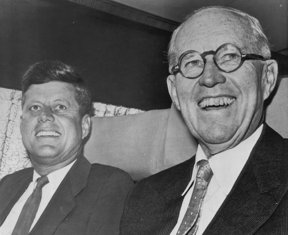 . Joseph P. Kennedy sits with his son President-elect, John F. Kennedy  aboard a jet as they prepared to take off for a series of conferences in New York, Washington and a meeting in Boston of the Board of Overseers of Harvard University, of which the president-elect is a member.