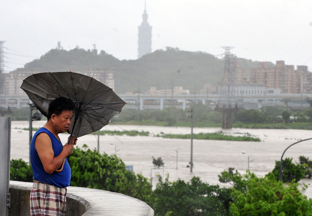 ". A resident battles against strong winds caused by typhoon Soulik in Taipei on July 13, 2013.  Thousands of people were evacuated in Taiwan and the entire island declared an ""alert zone\"" as Typhoon Soulik made landfall early morning, killing one person and injuring seven. Mandy Cheng/AFP/Getty Images"