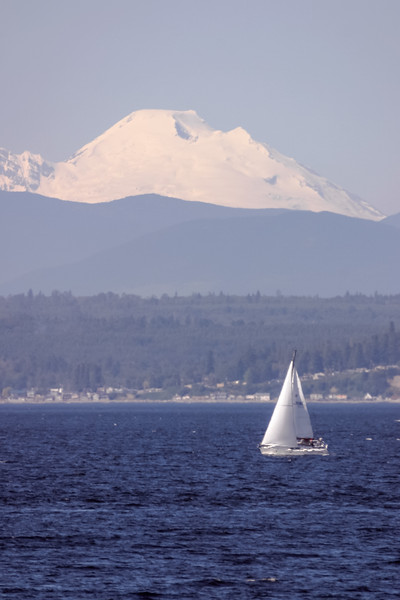Small sailboat in front of Mount Baker in Puget Sound near Everett, Washington