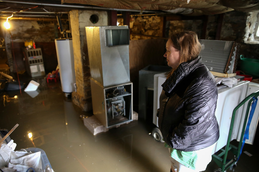 . Colleen Finnell, of Bellevue, Ky., surveys the damage of her flooded basement her Ward Avenue home, Sunday, Feb. 25, 2018. The Ohio River is expected to crest at 60.7 feet by Sunday evening, according to the National Weather Service. The river rose above the 60 feet mark for the first time in two decades Sunday morning.   (Kareem Elgazzar/The Cincinnati Enquirer via AP)