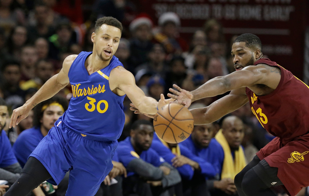 . Golden State Warriors\' Stephen Curry, left, and Cleveland Cavaliers\' Tristan Thompson battle for a loose ball in the first half of an NBA basketball game, Sunday, Dec. 25, 2016, in Cleveland. (AP Photo/Tony Dejak)