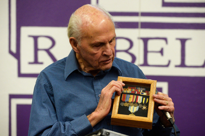 . WWII U.S. Navy veteran, Carl Hammergren, shows his medals and accommodations to South High School students during a living history lesson Wednesday morning, February 12, 2014. Three WWII veterans from the Clermont Park Retirement Community addressed U.S. History students and answered lots of questions. (Photo By Andy Cross / The Denver Post)
