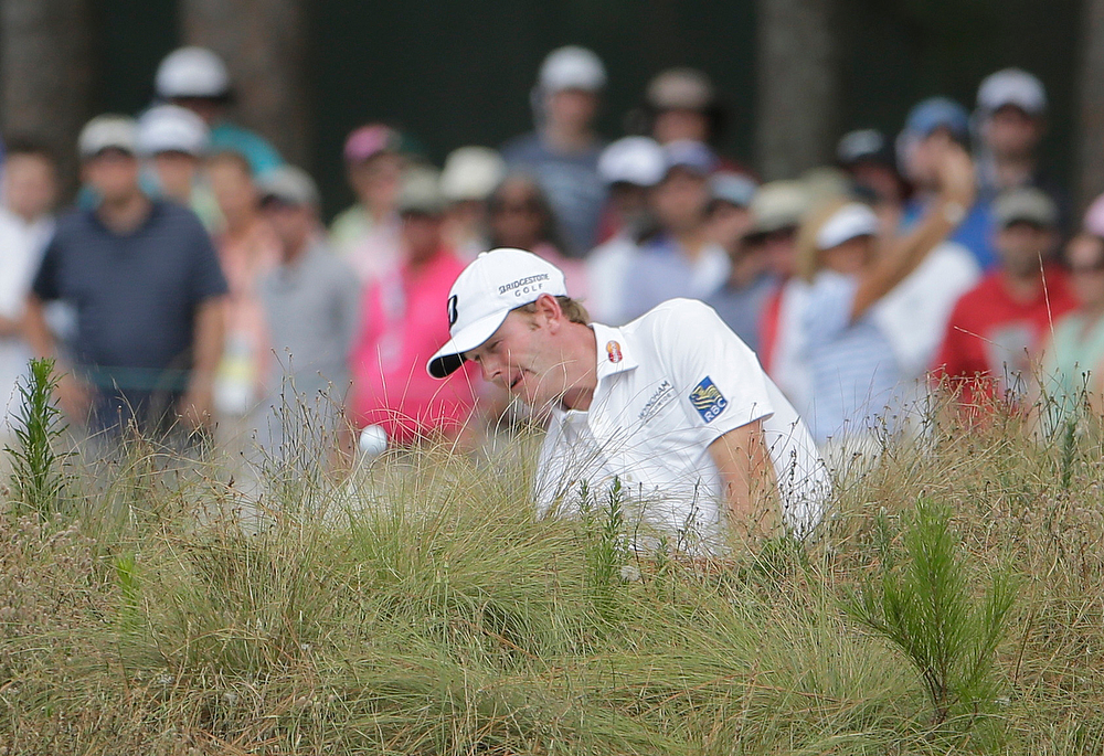 . Brandt Snedeker hits from the natural area on the seventh hole during the third round of the U.S. Open golf tournament in Pinehurst, N.C., Saturday, June 14, 2014. (AP Photo/Chuck Burton)