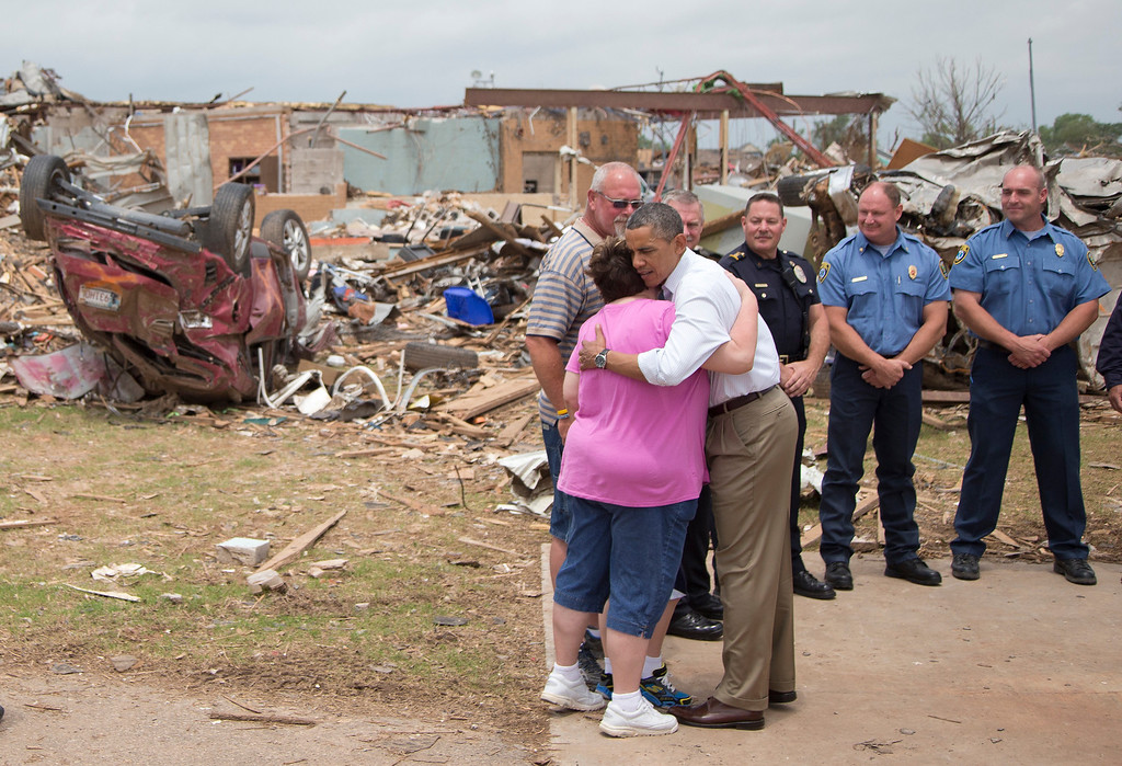 . President Barack Obama embraces Julie Lewis, seen with her husband Scott Lewis, and their son Zack, hidden, a third-grader of the destroyed Plaza Towers Elementary School seen in the background, as Obama visits Moore, Okla., Sunday, May 26, 2013, in Moore, Okla., which was utterly devastated by tornadoes and severe weather last week.  (AP Photo/Carolyn Kaster)