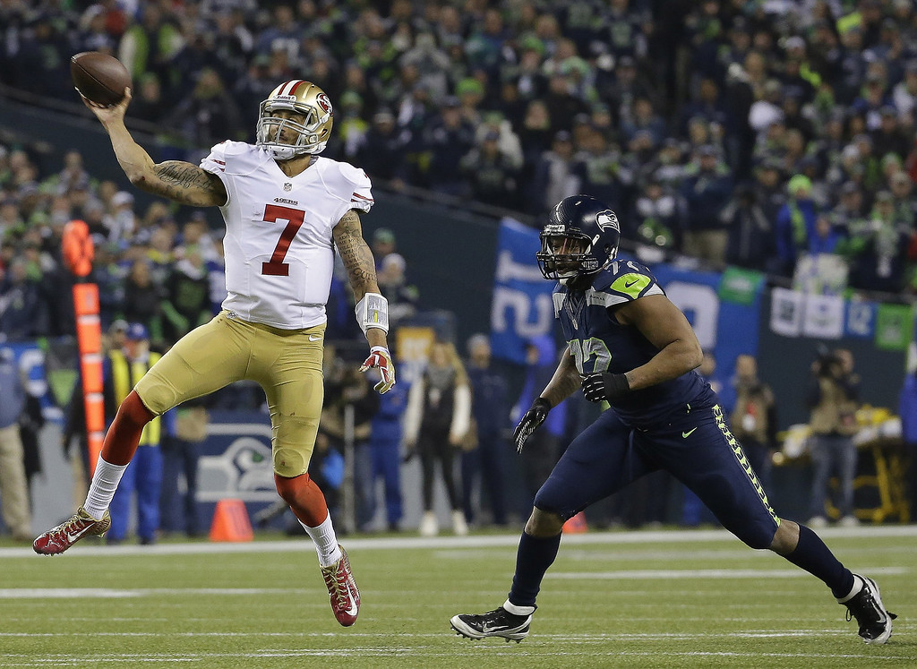 . San Francisco 49ers\' Colin Kaepernick throws with Seattle Seahawks\' Michael Bennett (72) rushing during the second half of the NFL football NFC Championship game Sunday, Jan. 19, 2014, in Seattle. (AP Photo/Ted S. Warren)
