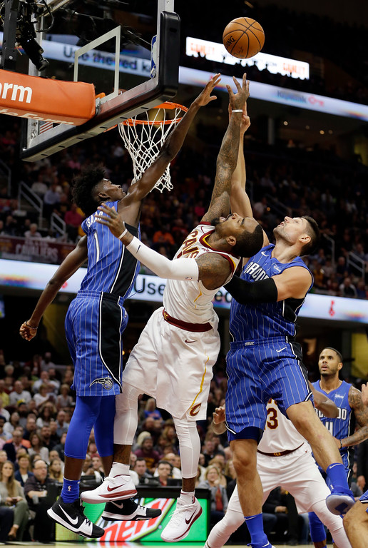 . Orlando Magic\'s Jonathan Isaac, left, and Orlando Magic\'s Nikola Vucevic, right, from Montenegro, battle for a rebound against Cleveland Cavaliers\' JR Smith, center, in the first half of an NBA basketball game, Saturday, Oct. 21, 2017, in Cleveland. (AP Photo/Tony Dejak)