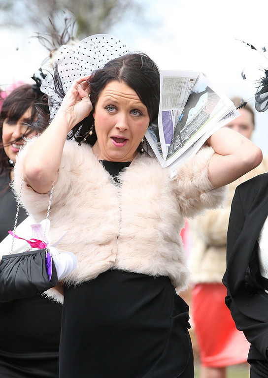 . A racegoer nearly loses her hat in the strong winds as she enjoys Ladies Day at Aintree on April 5, 2013 in Liverpool, England.  (Photo by Danny E. Martindale/Getty Images)