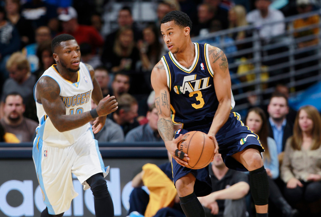 . Utah Jazz guard Trey Burke, right, pulls in a loose ball as Denver Nuggets guard Nate Robinson comes in to cover in the first quarter of an NBA basketball game in Denver on Friday, Dec. 13, 2013. (AP Photo/David Zalubowski)
