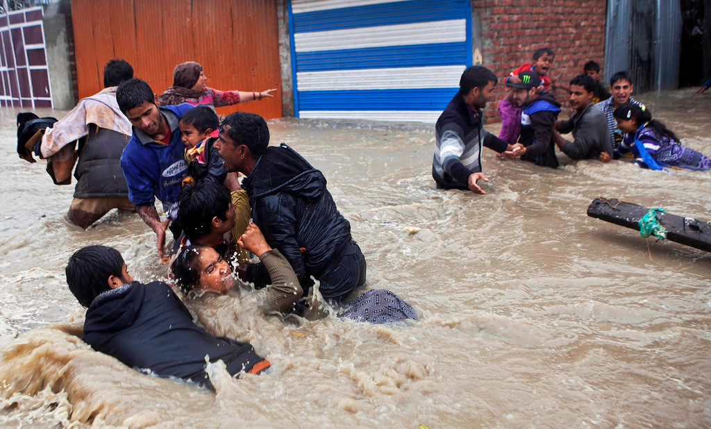 . Kashmiri residents wade through floodwaters in Srinagar, India, Thursday, Sept. 4, 2014. At least 100 villages across the Kashmir valley were flooded by overflowing lakes and rivers. (AP Photo/Dar Yasin, File)