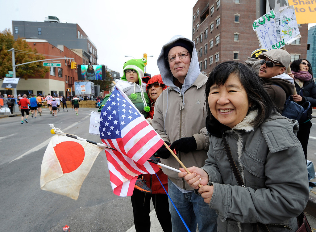 . Junko Savage and her husband, Gary Savage of Little Neck, N.Y., cheer runners as they come off the Pulaski Bridge in the Queens borough of New York during the New York City Marathon on Sunday, Nov. 3, 2013.  (AP Photo/Kathy Kmonicek)