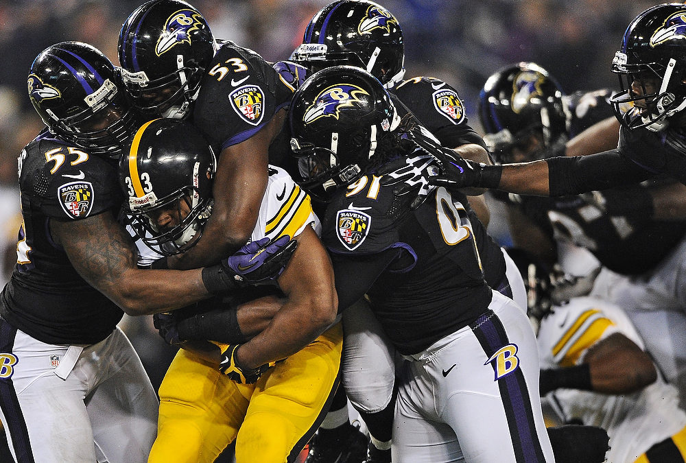 Description of . Running back Isaac Redman #33 of the Pittsburgh Steelers is pulled down by a pack of Baltimore Ravens defenders in the third quarter at M&T Bank Stadium on December 2, 2012 in Baltimore, Maryland. The Pittsburgh Steelers won, 23-20. (Photo by Patrick Smith/Getty Images)