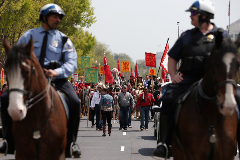 ". Members of the Cowboy and Indian Alliance, including Native Americans, farmers and ranchers from across the United States, are escorted by police as they march down Independence Avenue while demonstrating against the proposed Keystone XL pipeline April 22, 2014 in Washington, DC. As part of its ""Reject and Protect\"" protest, the Cowboy and Indian Alliance is organizing a weeklong series of actions by farmers, ranchers and tribes to show their opposition to the pipeline.  (Photo by Chip Somodevilla/Getty Images)"