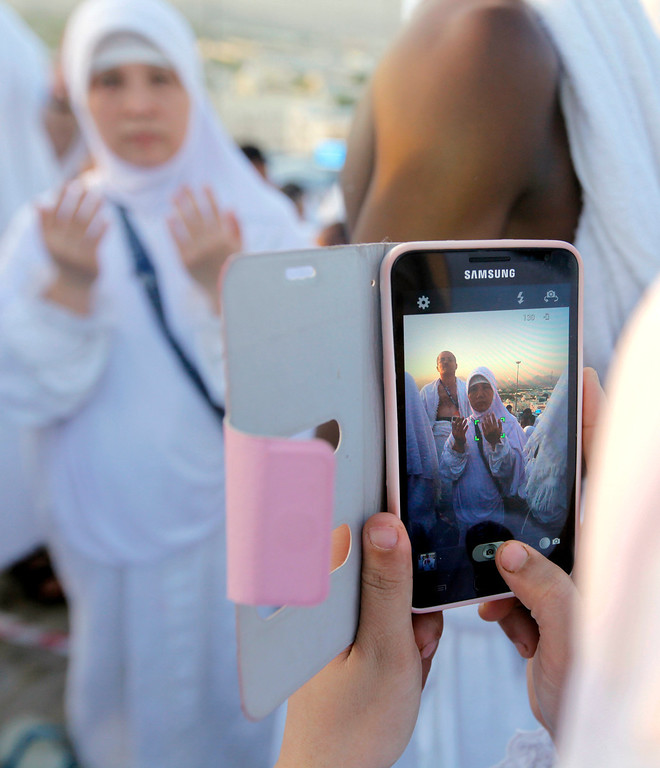 . An Indonesian Muslim pilgrim poses for a picture on a rocky hill called the Mountain of Mercy, near the holy city of Mecca, Saudi Arabia, Monday, Oct. 14, 2013.  (AP Photo/Amr Nabil)