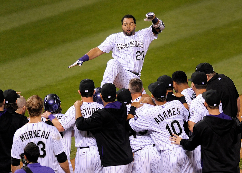 . Colorado Rockies\' Wilin Rosario leaps into his teammates arms after hitting a game-winning two-run home run in the ninth inning of a baseball game against the Arizona Diamondbacks Thursday, Sept. 18, 2014, in Denver. The Rockies won 7-6. (AP Photo/Chris Schneider)