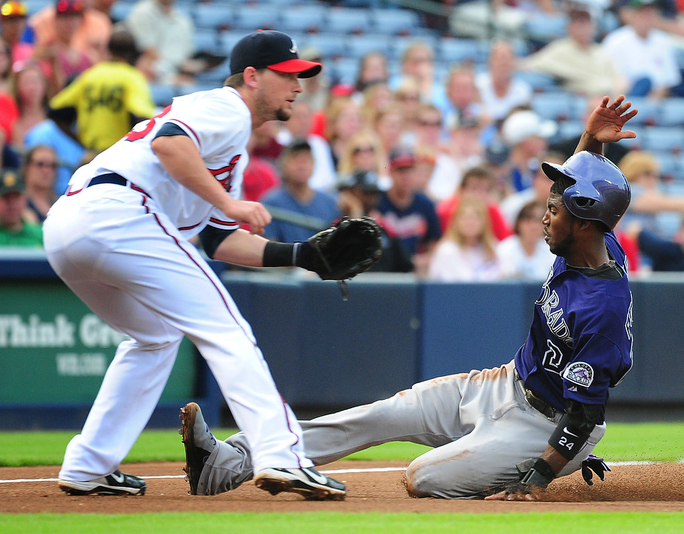 . Dexter Fowler #24 of the Colorado Rockies slides safely in to tird base against Chris Johnson #23 of the Atlanta Braves at Turner Field on July 30, 2013 in Atlanta, Georgia. (Photo by Scott Cunningham/Getty Images)