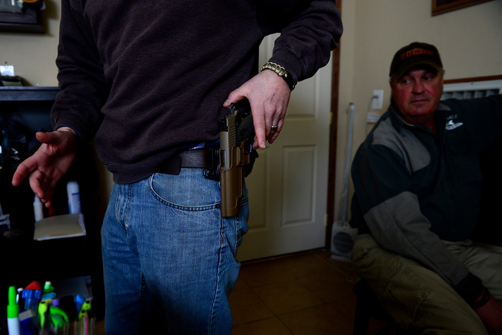 . ROCKY FORD, CO - FEBRUARY 25: Mac Holder shows off his .45 handgun, which he carries daily, as his father, Hal, looks on in an office at their store, Arkansas Valley Lumber and Supply in Rocky Ford. Gun owners in southern Colorado largely agree that responsible ownership begins at home. (Photo by AAron Ontiveroz/The Denver Post)