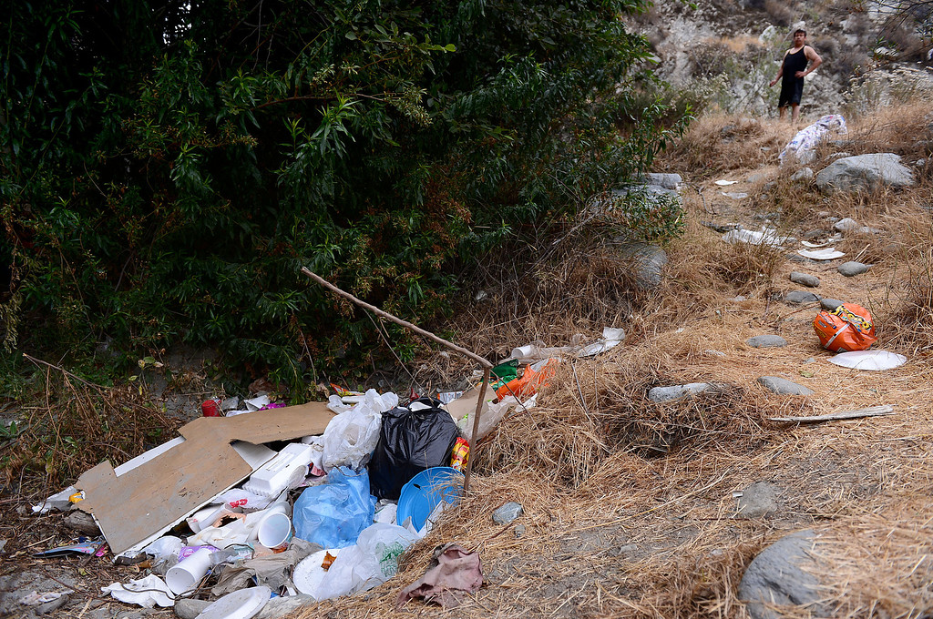 . Gary Romo, of Los Angeles, is in disbelieve at the piles of garbage he found after crossing the San Gabriel River along the East Fork in the Angeles National Forest Saturday, July 20, 2013 during his first visit to the area. The Urban Conservation Corps is trying to educate visitors and campers on packing their trash out in orange bags they hand out and breaking down dams for pools to avoid trapping the Santa Ana Sucker, a small fish that is listed as threatened. (SGVN/Staff Photo by Sarah Reingewirtz)