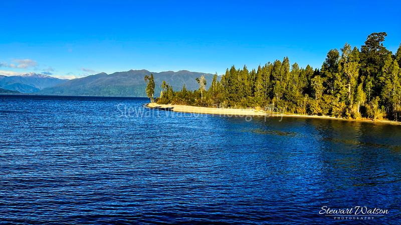 Tree lined Lake Brunner shore