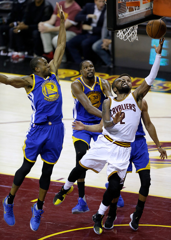 . Cleveland Cavaliers guard Kyrie Irving (2) drives against Golden State Warriors\' Andre Iguodala, left, and Kevin Durant (35) during the second half of Game 3 of basketball\'s NBA Finals in Cleveland, Wednesday, June 7, 2017. (AP Photo/Tony Dejak)
