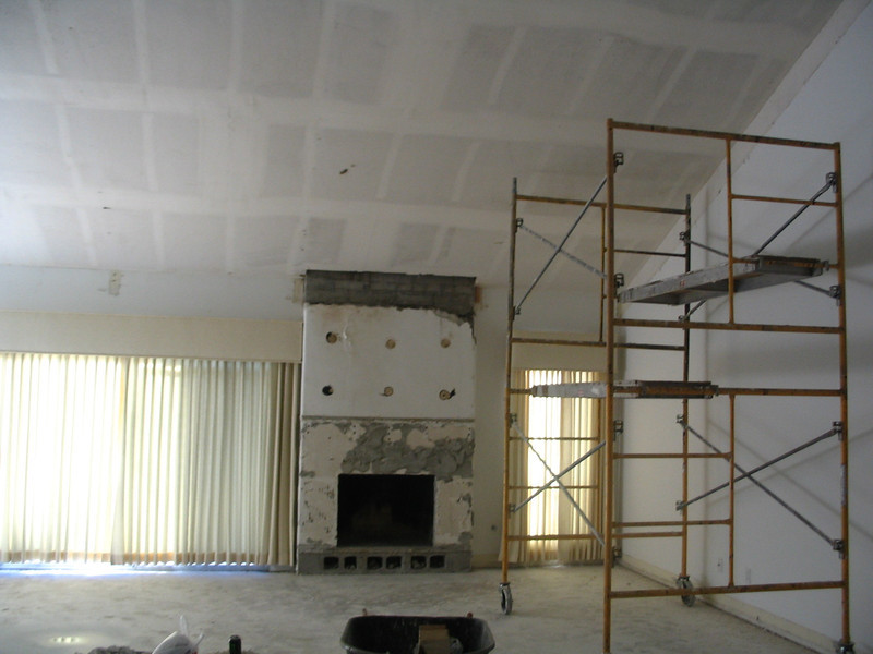The fireplace is going away (marble is already gone), and the beams on the ceiling (as well as the popcorn) have been removed.