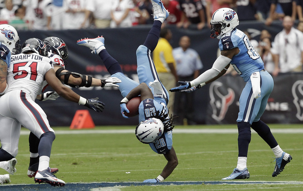 . Chris Johnson #28 of the Tennessee Titans is tripped up by Jared Crick #93 of the Houston Texans as Nate Washington #85 attempts to grab him at Reliant Stadium on September 15, 2013 in Houston, Texas. (Photo by Bob Levey/Getty Images)
