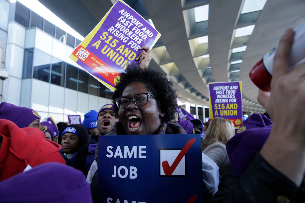 . Protesters gather at Chicago\'s O\'Hare International Airport on Tuesday, Nov. 29, 2016, as part of a nationwide protest for a $15 per hour minimum wage. Fast-food restaurant and airport workers, as well as home and child-care workers rallied in cities including Chicago, Detroit, Houston, Los Angeles, Minneapolis and New York on Tuesday morning. (AP Photo/Kiichiro Sato)