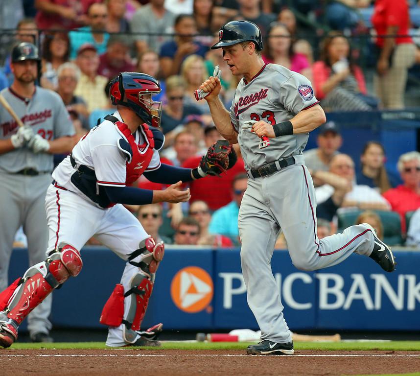 . Minnesota\'s Justin Morneau scores past Atlanta Braves catcher Brian McCann on an RBI single by Pedro Florimon during the second inning. (Curtis Compton/Atlanta Journal-Constitution/MCT)
