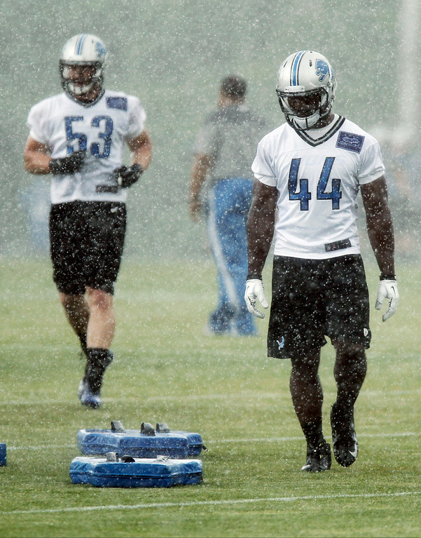 . Detroit Lions linebackers Justin Jackson (44), and Corey Greenwood (53) move to another drill during a downpour on the final day of minicamp Thursday, June 12, 2014, in Allen Park, Mich. (AP Photo/Duane Burleson)