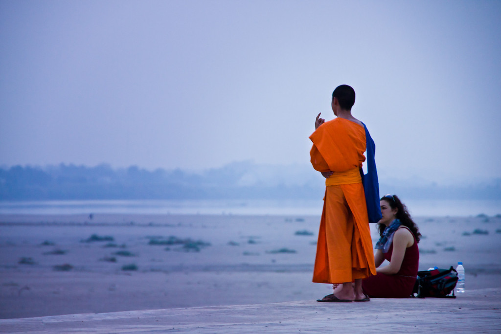 A monk chatting with a tourist by the Mekong river in Vientiane, Laos.