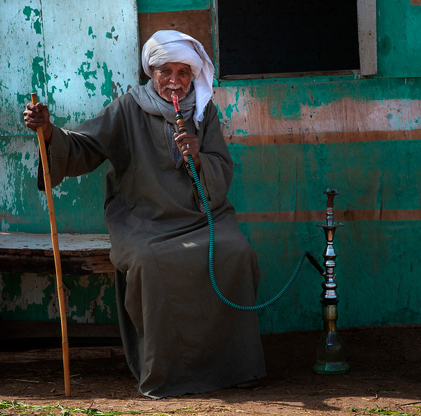 Camel owner smoking shisha (water pipe).  Birqash camel market, Cairo, Egypt, 2010.