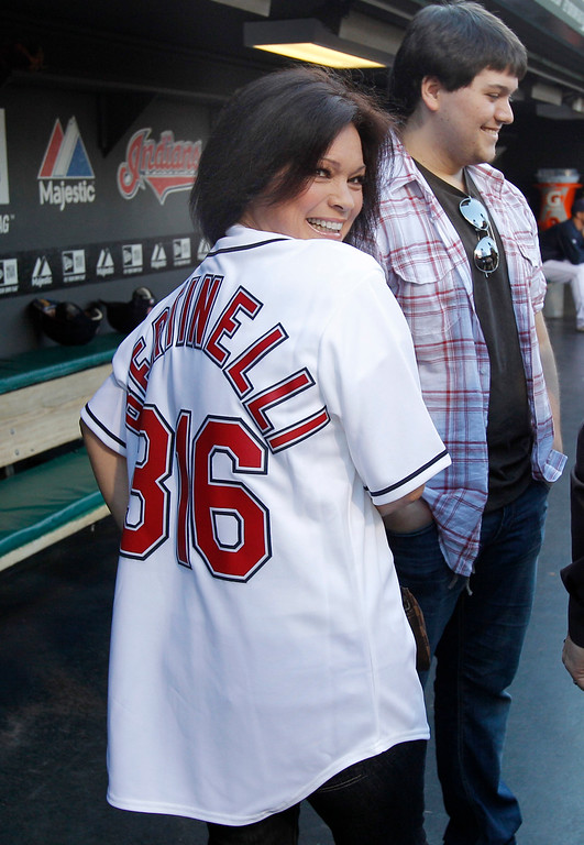 . Actress Valerie Bertinelli of the sitcom \'Hot in Cleveland\' shows off her Cleveland Indians jersey before throwing a ceremonial first pitch before the Cleveland Indians face the Pittsburgh Pirates in a baseball game in Cleveland on Friday, June 17, 2011.  With her in the dugout is her son Wolfgang Van Halen.  (AP Photo/Amy Sancetta)