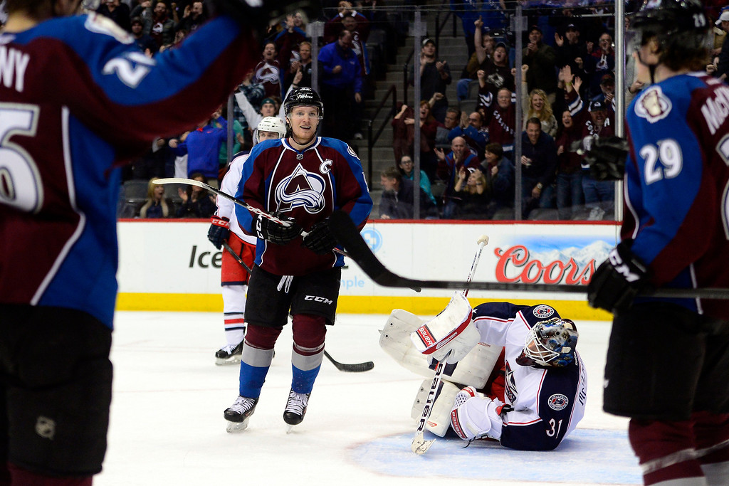 . Gabriel Landeskog (92) of the Colorado Avalanche looks to congratulate teammate Nathan MacKinnon (29) on his 5-3 goal as Curtis McElhinney (31) of the Columbus Blue Jackets lies on the ground during the third period of Colorado\'s 5-3 win. (Photo by AAron Ontiveroz/The Denver Post)
