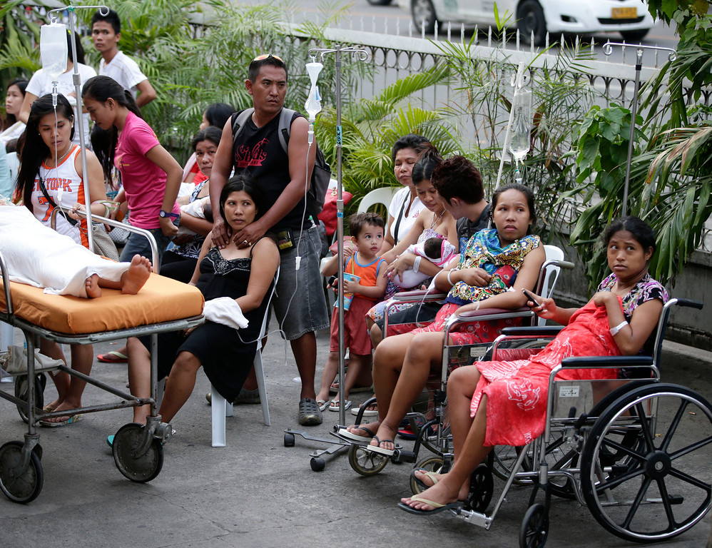 . Patients stay outside a hospital to avoid aftershocks following a 7.2-magnitude earthquake that hit Cebu city in central Philippines Tuesday, Oct. 15, 2013.  (AP Photo/Bullit Marquez)