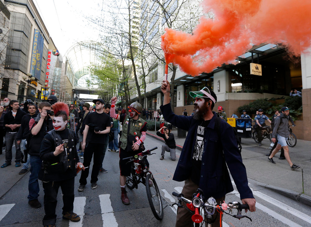 . A protester in clown make-up holds a smoke device during a May Day march that began as an anti-capitalism protest and turned into demonstrators clashing with police Wednesday, May 1, 2013, in downtown Seattle. (AP Photo/Ted S. Warren)