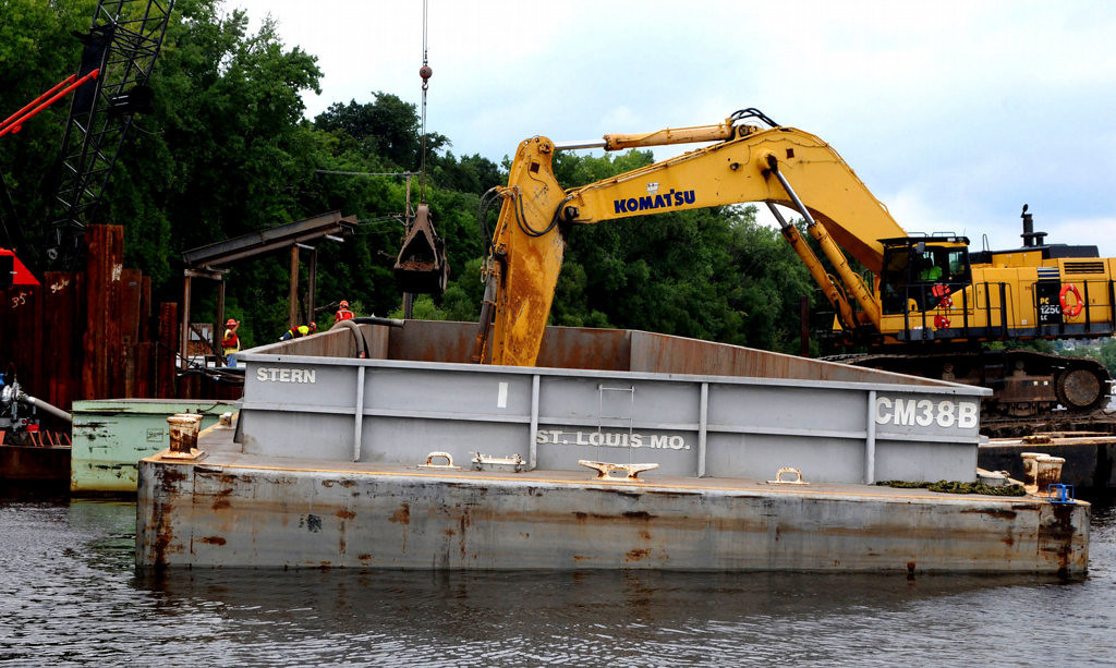 . Material excavated from the bottom of the St. Croix River is transferred from a barge to a truck for disposal. Some of the sand and gravel could be used to build the approach on the Wisconsin side of the river. By the time the five piers in the river are complete, 25,000 cubic yards of muck, sand and gravel will have been dredged up. (Pioneer Press: John Doman)