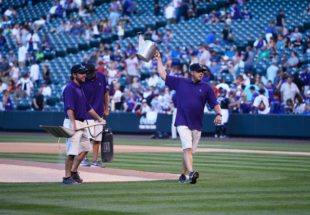 . DENVER, CO. - AUGUST 16:  Colorado Rockies assistant grounds keeper, Jason Garner, right, raises a watering can asking for a refill from the Cincinnati Reds dugout to water down home plate at Coors Field Saturday evening, August 16, 2014. The Rockies were set to play the Cincinnati Reds but the game was cancelled due to a water main break along Blake St, out in front of Coors Field, cutting off water supply to the stadium. (Photo By Andy Cross / The Denver Post)