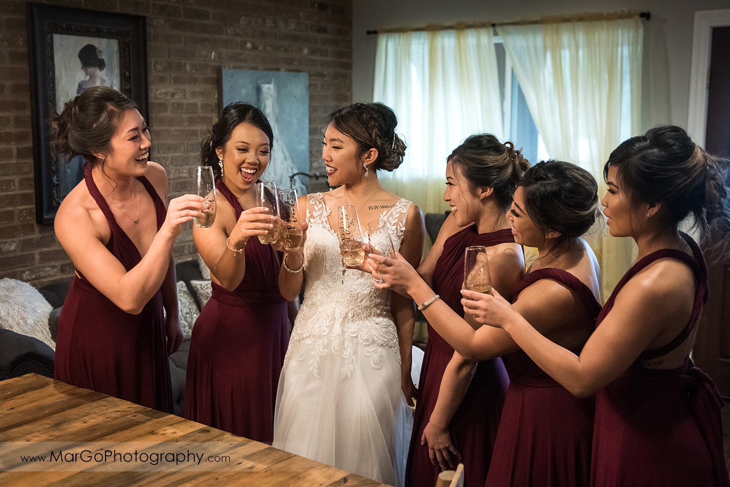 bride and bridesmaids drinking champagne  at Sunol's Casa Bella bridal suite