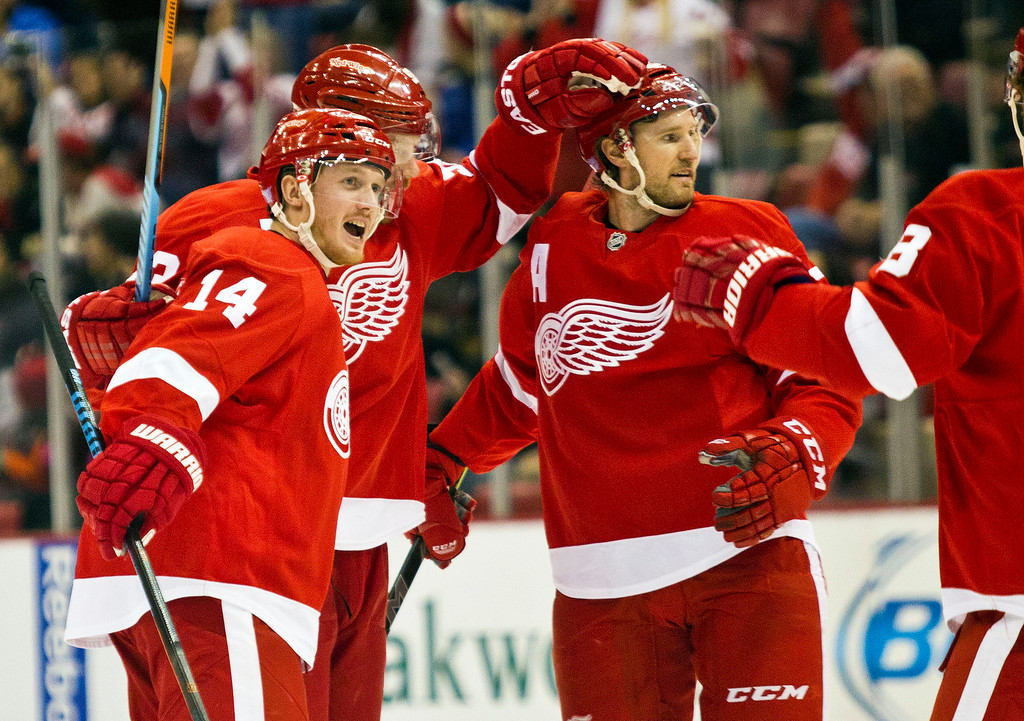 . From left to right, Detroit Red Wings forward Gustav Nyquist (14), forward Johan Franzen and defenseman Niklas Kronwall, all of Sweden, celebrate a goal during the first period of an NHL hockey game against the Tampa Bay Lightning in Detroit, Mich., Sunday, Nov. 9, 2014. (AP Photo/Tony Ding)
