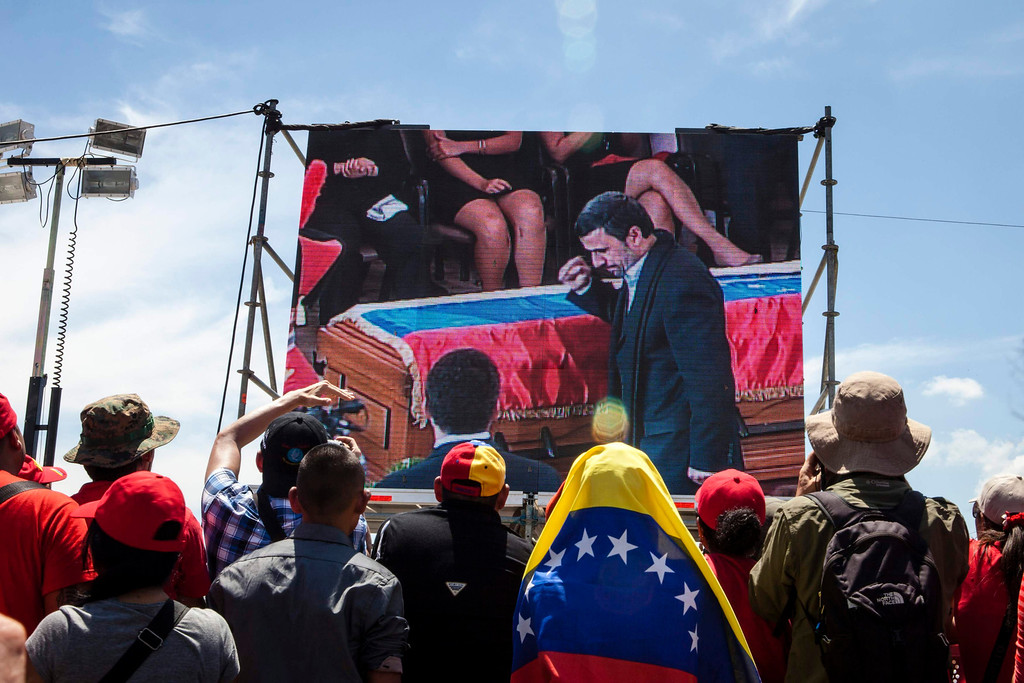 . Supporters of Venezuela\'s late President Hugo Chavez watch a screen as Iran\'s President Mahmoud Ahmadinejad walks past Chavez\'s coffin during the funeral ceremony, outside the Military Academy in Caracas March 8, 2013.  REUTERS/Marco Bello