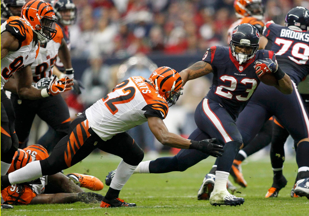 Description of . Houston Texans running back Arian Foster breaks a tackle by Cincinnati Bengals strong safety Nate Clements in the second quarter during their NFL AFC wildcard playoff football game in Houston, Texas January 5, 2013. REUTERS/Mike Stone