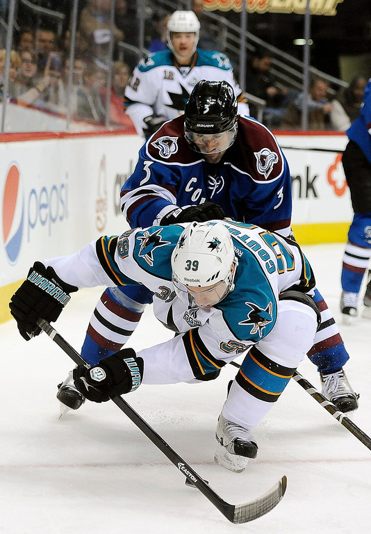 . San Jose Sharks center Logan Couture, front, tries to keep the puck away from Colorado Avalanche defenseman Ryan O\'Byrne, rear, in the second period of an NHL hockey game on Sunday, March 10, 2013, in Denver.  (AP Photo/Chris Schneider)