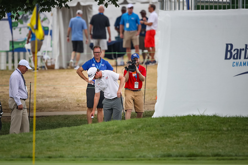 JT Poston on the 9th hole after hitting his tee shot in between the stands.