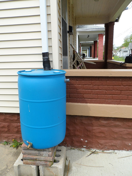A rain barrel for the Boston Court community garden is attached to the home of Save a House/Make a Home homeowner partner Louis Alexander.