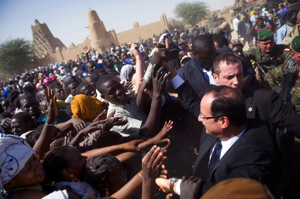 Description of . Security surrounds France\'s President Francois Hollande (R) who is welcomed by Malians  during his arrival at Timbuktu during his one-day visit in Mali on February 2, 2013. French President Hollande flew to Mali on Saturday to support French troops fighting Islamist rebels in the Sahel nation and he visited the famed ancient city of Timbuktu that was recaptured from al Qaeda-allied fighters six days ago. REUTERS/Fred Dufour/Pool
